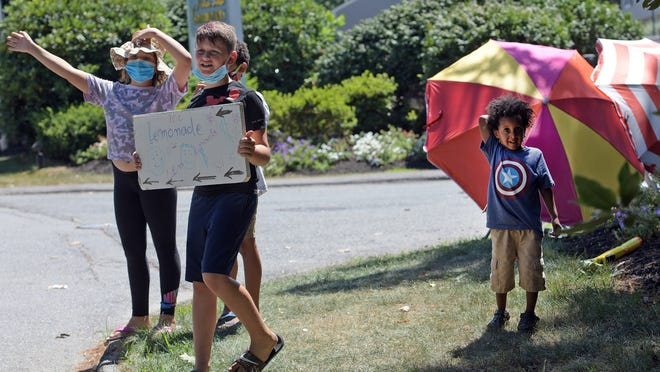 Taj Chekalard, 8, Mikhail Bitar, 10,  Julien Appiah, 8, and Jeremiah Appiah, 3, wave at motorists Sunday from their lemonade stand on Sunderland Road in Worcester.