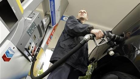 James Lewis pumps gas at a station in Portland, Ore. Even after the typical springtime run-up, the average price for gallon of regular gasoline should top out around $2.60, experts say.
