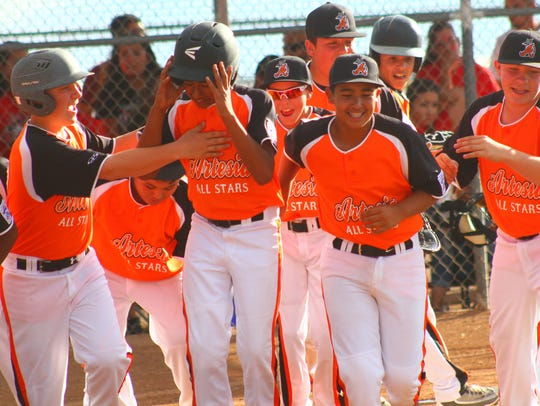 Artesia players celebrate after Matthew Chavez hit