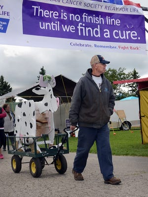Gary Humrich pulls the Country Cousins team mascot around the walking track at the Fowlerville Relay For Life last weekend at the Fowlerville Fairgrounds. The mascot was introduced some 15 years ago and was the brainchild of cancer survivor Mary Johnson. Her husband, Jon, created the product.