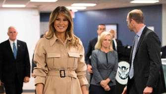 First lady Melania Trump chose a khaki belted trench coat and her usual towering heels for her first appearance in public in 27 days, and following a five-day hospital stay for successful treatment of a kidney condition. She accompanied President Trump to a Washington briefing on 2018 hurricane preparations.
