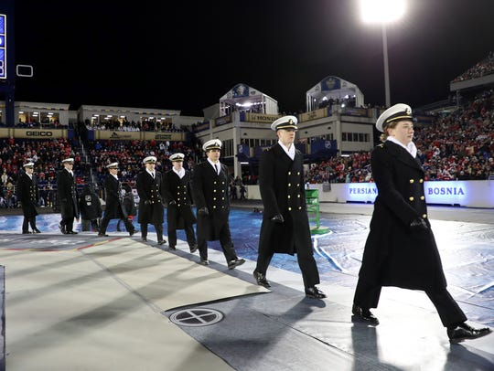 U.S. Navy Midshipmen march onto the field of play before