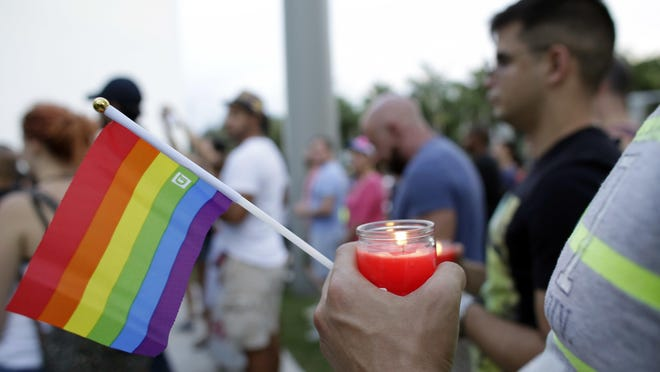 A man holds a candle and a rainbow flag during a vigil in memory of the victims of the Orlando mass shooting, in Miami Beach, Florida, on Sunday. A gunman opened fire inside a crowded gay nightclub early Sunday, before dying in a gunfight with SWAT officers, police said.