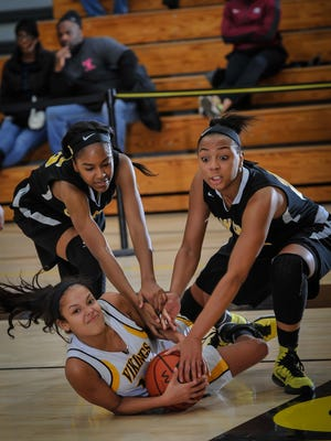 South Brunswick's Gillian Chambers (center) fights for the loose ball with Piscastaway's Kendrea Williams (left) and Nadia Wooten in their game at South Brunswick High School on Jan. 12, 2016. Photo by Jeff Granit