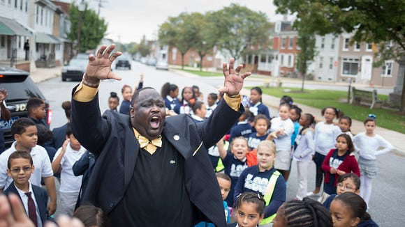 Lincoln Charter School Principal Leonard Hart roars like a lion, the school's mascot, during the school's celebration for International Walk to School Day earlier this month in York. Hart has made his school a large part of the Salem Square Neighborhood Association's application process seeking an Elm Street designation for the neighborhood on the city's west end.