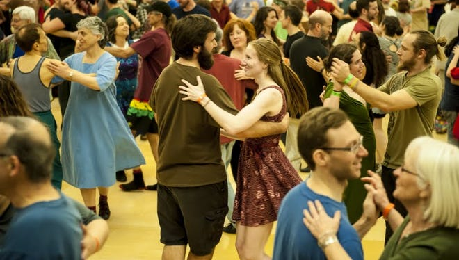 Dancers of all ages and experience levels enjoy themselves at a group dance.