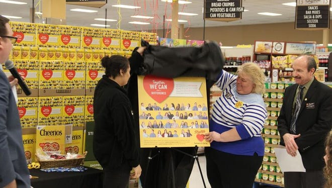 ShopRite of Fishkill Associates Kelsey Wright, left, and Dawn Doughty-Myers unveil a poster depicting the special edition Cheerios box featured now in ShopRite stores. Both women got their photos on the Cheerios box as part of the ShopRite Partners In Caring Cheerios contest that raised $1.4 million to fight hunger in the communities served by ShopRite stores.