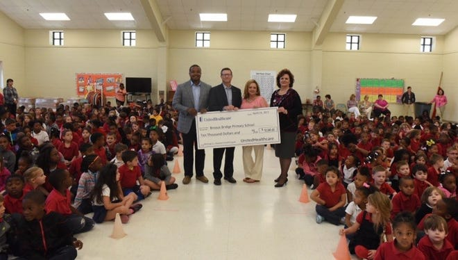 "Dreambuilders Foundation captain and former LSU MVP Justin Vincent, UnitedHealthcare-Gulf States CEO Joe Ochipinti present a check for $10,000 for Breaux Bridge Primary School's ""Blessings in a Backpack"" Meal Program to Breaux Bridge Primary School Principal Jill Bozeman and St. Martin Parish Schools Superintendent Dr. Lottie Beebe."