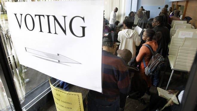 FILE- In a Nov. 3, 2008, file photo, voters wait to fill out absentee ballots the day before the general election in Detroit. Absentee ballot voting has been greatly expanded in Michigan in 2020.