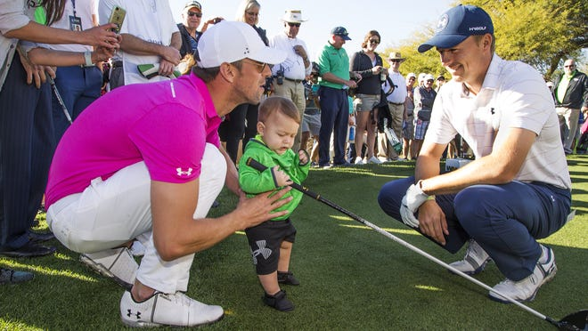 Michael Phelps, left, steadies his son Boomer after professional golfer Jordan Spieth, right,  handed the toddler his driver on the third tee of the Annexus Pro-Am at the 2017 Waste Management Phoenix Open at TPC Scottsdale, Wednesday, February 1, 2017.