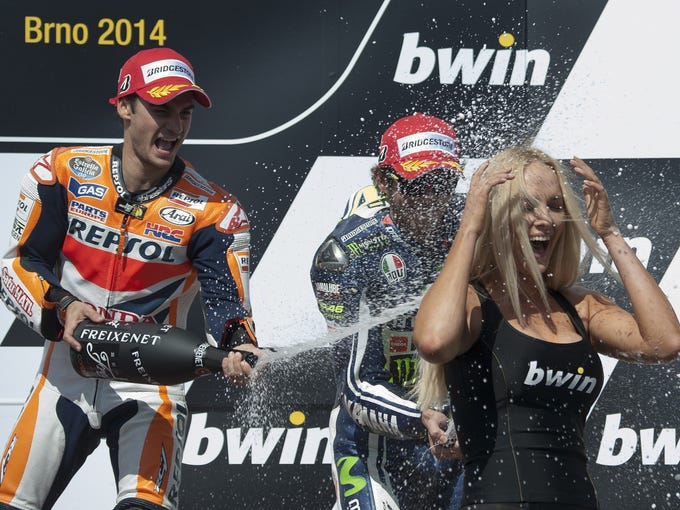 Repsol Honda Team's Spanish rider Dani Pedrosa (L) and Yamaha Factory MotoGP's Italian rider Valentino Rossi spray champagne as they celebrate on the podium after the Moto GP of the Czech Republic's Grand Prix on August 17, 2014 in Brno, Czech Republic. Pedrosa won the race ahead of Yamaha Factory Racing's Spanish rider Jorge Lorenzo (2nd) and Yamaha Factory MotoGP's Italian rider Valentino Rossi (3rd). AFP PHOTO / MICHAL CIZEK        (Photo credit should read MICHAL CIZEK/AFP/Getty Images)