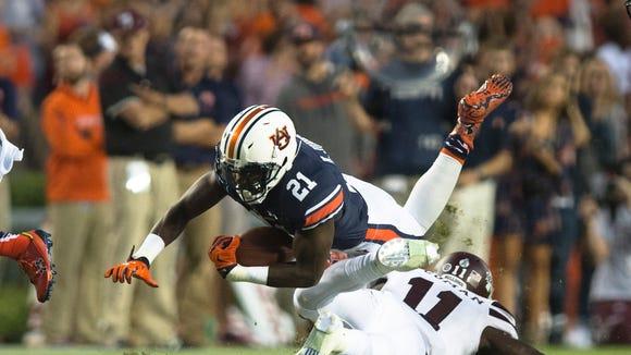 Auburn running back Kerryon Johnson (21) dives over
