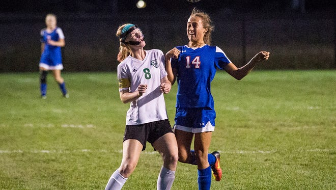 Jay County's Breea Liette heads the ball past Yorktown's Mercedes McGraw during their game at the Yorktown Sports Park Tuesday, Oct. 4, 2016.