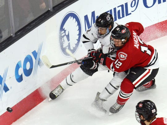 Nebraska Omaha's David Pope (left) and St. Cloud State defenseman Jack Ahcan (12) battle for the puck during the first period Saturday at Baxter Arena in Omaha, Nebraska.