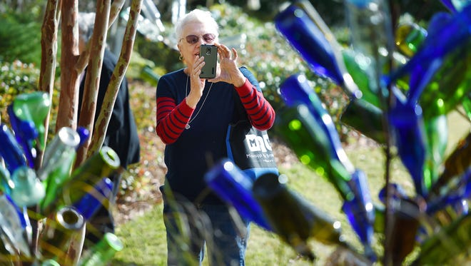 Virginia Lee Cora snaps a photo while touring the Festivus Bottle Tree Art Orchard in the Mississippi Museum of Art's Walker Garden on Thursday.