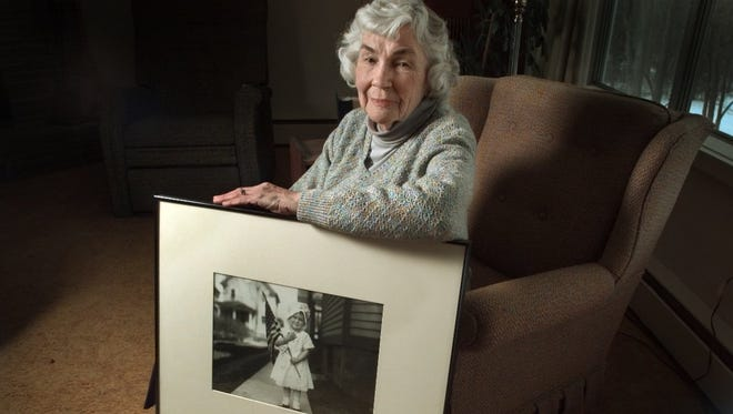 Helen Stone Reinhard holds a photo of herself at age 4 that was taken by her grandfather Albert Stone in front of her Sherman Street home in 1919. The collection of Albert Stone's many years of work as a newspaper photographer in Rochester, including 14,000 glass plates, is in the care of the Rochester Museum and Science Center.