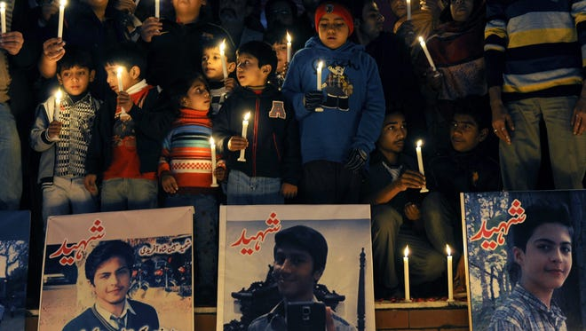 People light candles around pictures of some of those killed in an attack on an army-run Peshawar school in Islamabad on Dec. 18, 2014.
