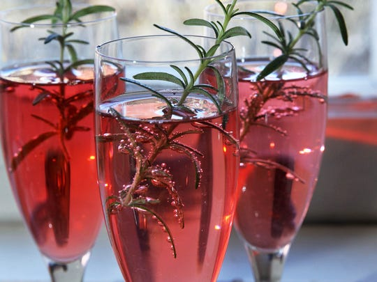 The Cranberry Prosecco Fizz gets a holiday touch with a sprig of rosemary