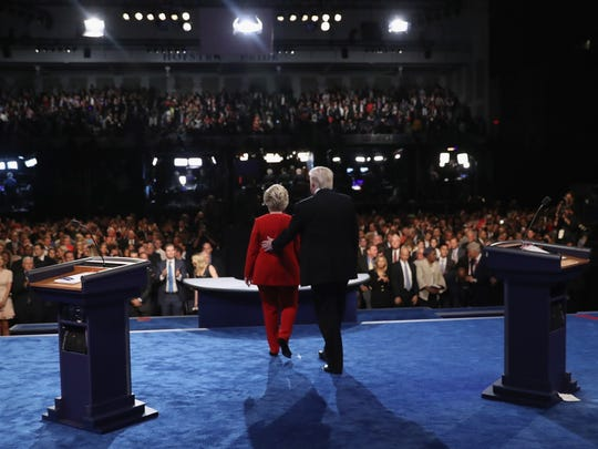 Democratic presidential nominee Hillary Clinton (left) and Republican presidential nominee Donald Trump leave the stage after the presidential debate at Hofstra University.