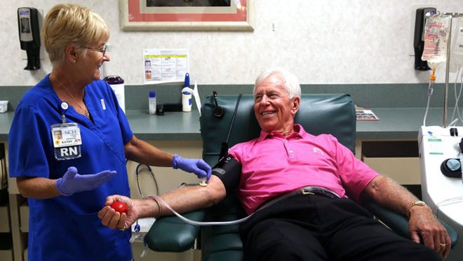 Registered nurse Kathy Moore, left, prepares Bill Hall, 75, of Naples, Fla., for his 438th blood or blood product donation April 18, 2016.