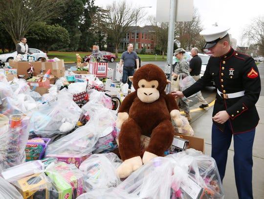 Lance Cpl. Jorin Hollenbeak helps load thousands of