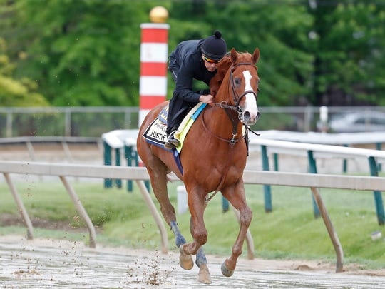 Kentucky Derby winner Justify, ridden by exercise rider Humberto Gomez, participates in a morning workout in preparation for the 143rd Preakness Stakes at Pimlico Race Course.