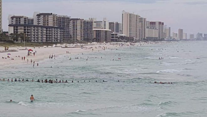Dozens of beachgoers at Panama City Beach, Fla., form a human chain to rescue nine stranded swimmers swept away by a strong riptide on Saturday.