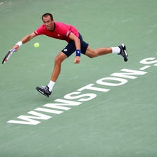 Lukas Rosol of the Czech Republic returns a shot to Yen-Hsun Lu of Tawain during the men's semifinal match of the Winston-Salem Open at Wake Forest University.