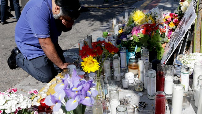 Jose Cardoso pays his respects May 25 at a makeshift memorial in front of the IV Deli Mart, where part of a mass shooting took place near Santa Barbara.