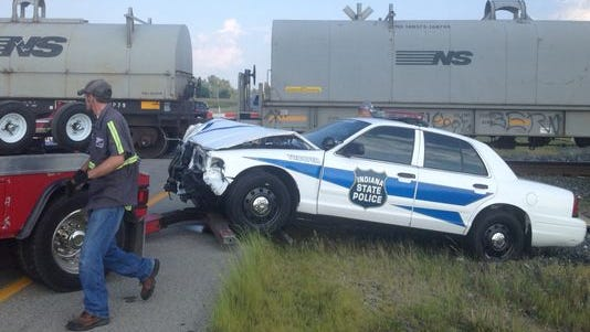 An Indiana State Police car is towed from the scene after colliding with a Norfolk Southern train Friday afternoon.