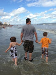 Ryan Goss walks with his two children in this family