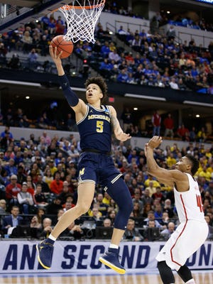D.J. Wilson #5 of the Michigan Wolverines lays it up for a shot against Donovan Mitchell #45 of the Louisville Cardinals in the first half during the second round of the 2017 NCAA Men's Basketball Tournament at the Bankers Life Fieldhouse on March 19, 2017 in Indianapolis, Indiana.