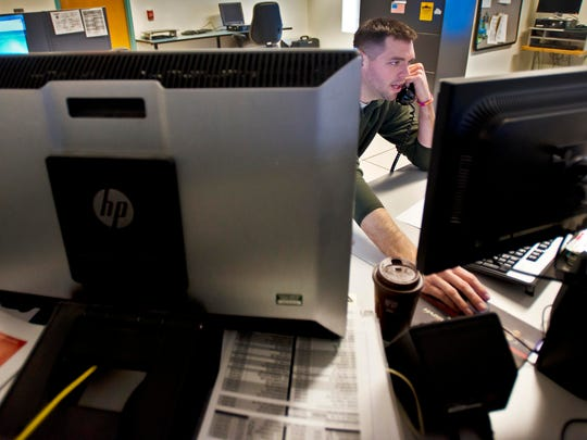 Mike Taptick takes a call at the 911 call and dispatch center at the Vermont State Police barracks in Williston on Friday.