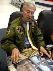 Capt. C. Flack Logan flips through photographs from