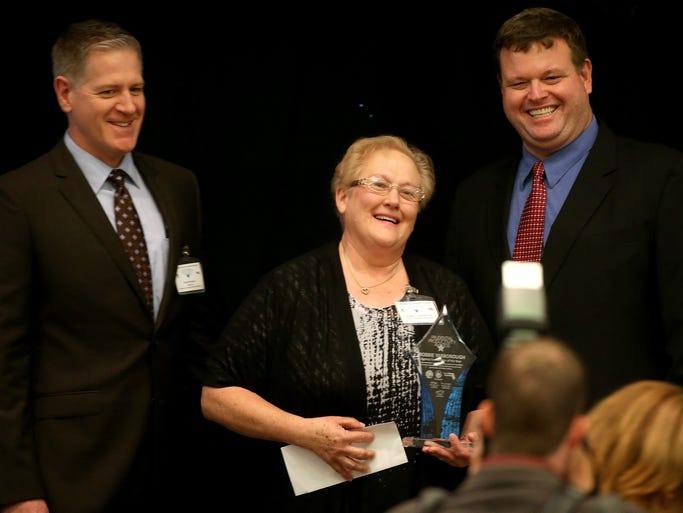 Robbie Yarborough, center, shares a laugh with DEP colleagues Lennie Zeiler, right, and Bob Wilson after she was presented with the Prudential Productivity Award for Coordinator of the Year during the 2014 Tallahassee Prudential Productivity Award luncheon.