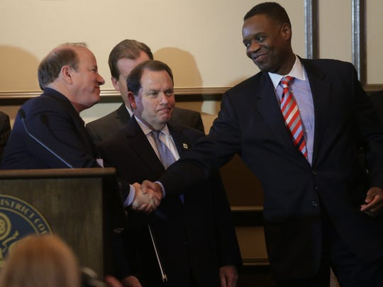 Emergency Manager Kevyn Orr shakes the hand of Detroit Mayor Mike Duggan while speaking to the press Friday, Nov. 7, after Judge Steven Rhodes approval of Detroit's historic restructuring plan.