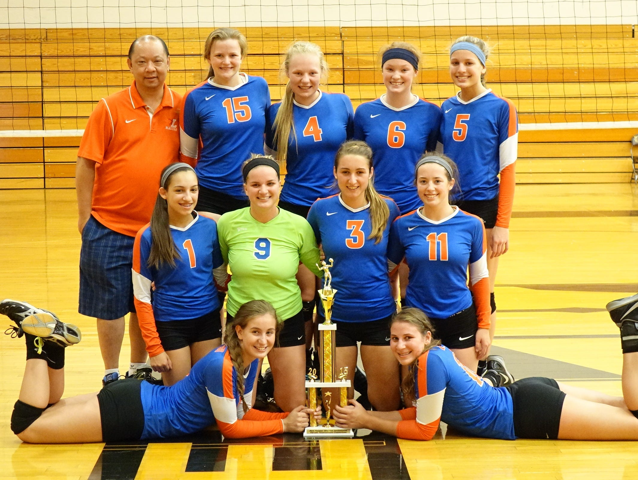 Members of Livonia Ladywood's volleyball team pose with the second first-place trophy they secured in the past two weeks.