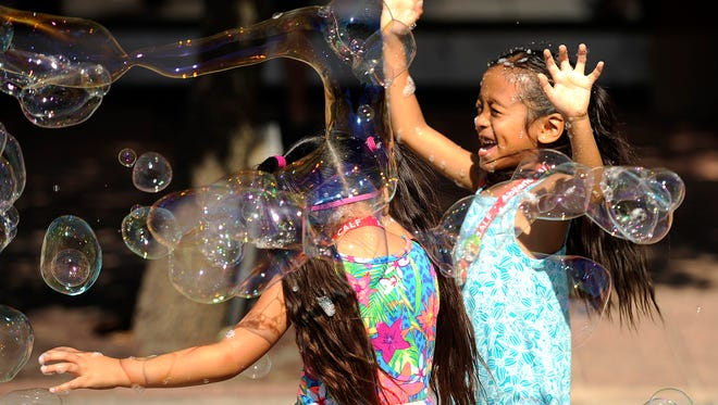 Julie Phleuy (right), 6, and her sister, Kylie, 5, play in the bubbles during the Children's Art & Literacy Festival on Saturday, June 10, 2017, in downtown Abilene.