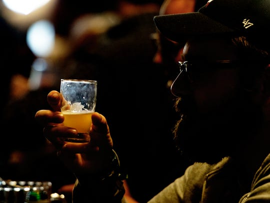 A patron tries a beer during a beer bottle share at Suttree's in Knoxville, Tennessee on Saturday, March 25, 2017. A crowd of around 100 people shared beers from throughout the world including craft beers and speciality beers.