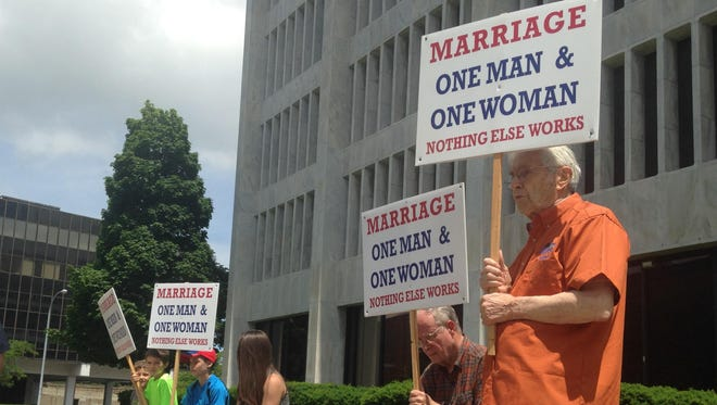 Michael Macaluso, right, carries a sign at a traditional marriage rally in Rochester Saturday.