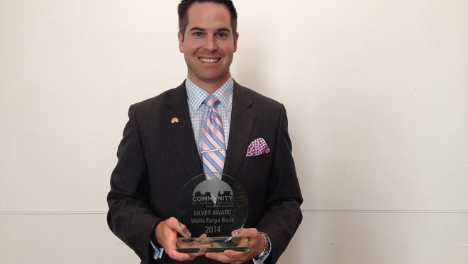 Tony Dickinson, vice president of marketing at Wells Fargo, accepts the IBA Community Betterment Silver Award Tuesday, Sept. 23.