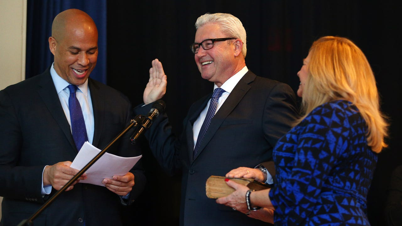Mayor Tim Dougherty is sworn in to his third term by U.S. Senator Cory Booker as Dougherty's wife Mary holds the Bible during Morristown's 2018 reorganization meeting at the Thomas Jefferson School.
