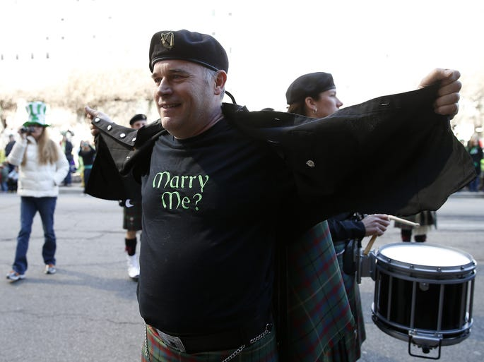 The Emerald Society Pipe Band piper Tommy Thompson takes off his shirt surprising his girlfriend Tish Jones, both of Hebron, Ky. with a marriage proposal during the annual Cincinnati St. Patrick's Day Parade downtown.