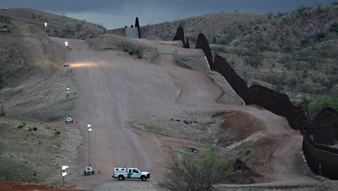 In this April 22, 2010, file photo, a Customs and Border Patrol agent patrols along the international border after sunset in Nogales, Ariz.