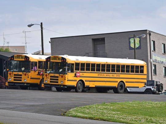 Buses sit in the parking lot of New Vision Academy on May 18, 2018. The school is under investigation for misspent funds, including on bus transportation, and will now need to relocate students after being found out of compliance with fire codes.