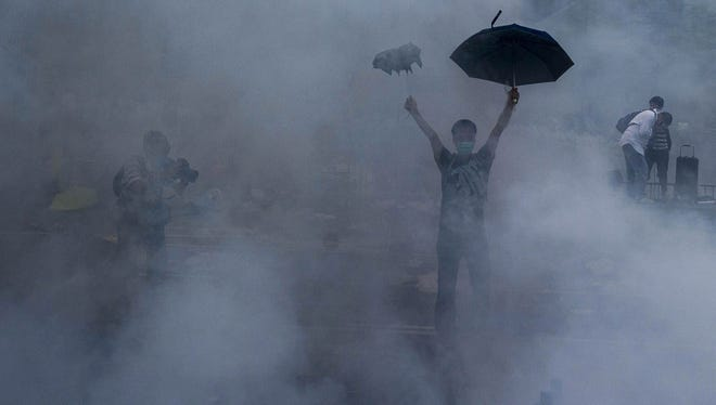 A Hong Kong protester reacts to police firing tear gas Sunday.