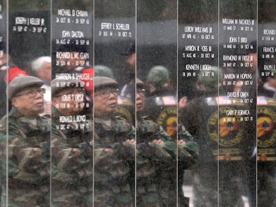 Vietnam veteran Pran Chinh, Cherry Hill, is reflected in the walls of the New Jersey Vietnam Veterans' Memorial in Holmdel during the Veterans Day Ceremony there Wednesday, November 11, 2015.