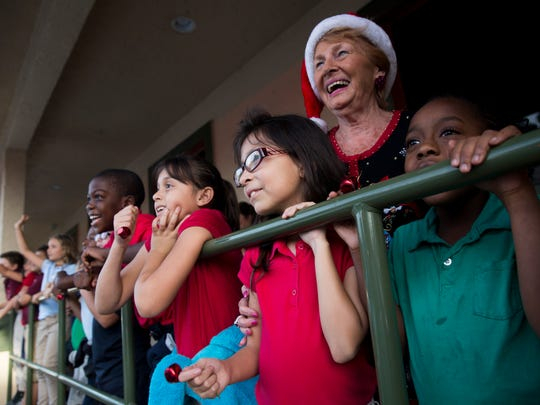 Jenneyah Poulard, 7, from right, and Sophia Lubr, 7, patiently wait for the arrival of Santa Claus with Elk Lodge member Maryann Giglio during the 4th annual Children's Christmas Party for second graders from Manatee Elementary School Monday, Dec. 12, 2016 at the fraternities lodge in East Naples.