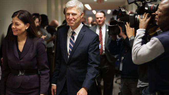 Supreme Court nominee Judge Neil Gorsuch (center) is accompanied by former Republican Sen. Kelly Ayotte (left) as they arrive for a meeting at the office of Sen. Joe Manchin (D-W.Va.) in the Hart Senate Office Building on Capitol Hill on Wednesday.