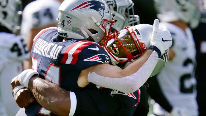 New England Patriots quarterback Cam Newton, right, gives running back Rex Burkhead a lift after Burkhead's touchdown in the second half of an NFL football game against the Las Vegas Raiders, Sunday, Sept. 27, 2020, in Foxborough, Mass.